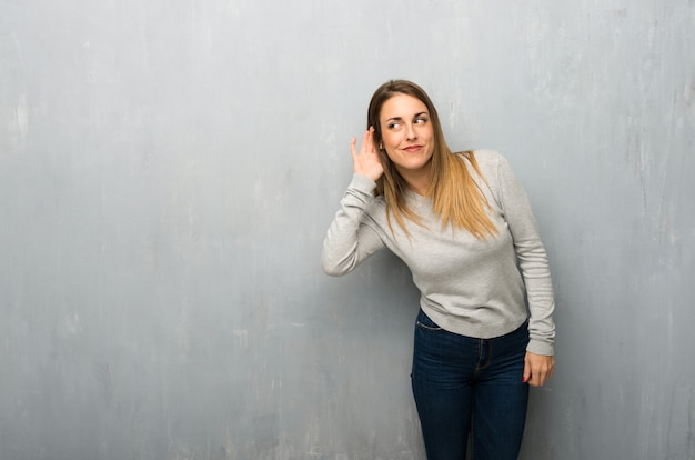 Jeune femme, mur texturé, écoute, quelque chose, mettre, main, oreille Photo Premium