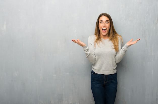 Jeune femme sur un mur texturé avec expression faciale surprise et choquée Photo Premium