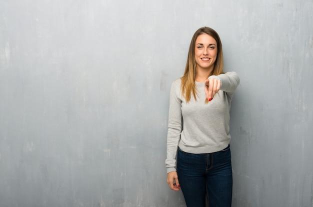 Jeune femme sur un mur texturé pointe le doigt vers vous avec une expression confiante Photo Premium