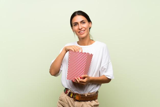 Jeune Femme Sur Un Mur Vert Isolé, Tenant Un Bol De Pop-corn Photo Premium