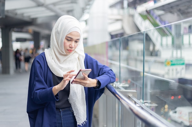 Jeune femme musulmane à l'aide de smartphone. Photo Premium
