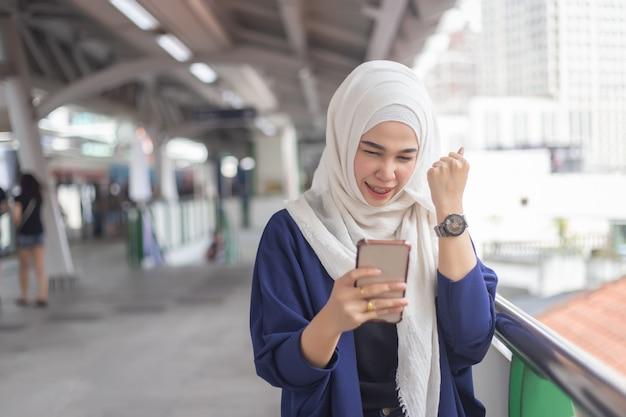 Jeune femme musulmane à l'aide de téléphone sur la station de skytrain. Photo Premium