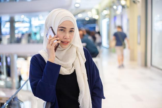 Jeune femme musulmane à l'aide de téléphone en supermarché. Photo Premium