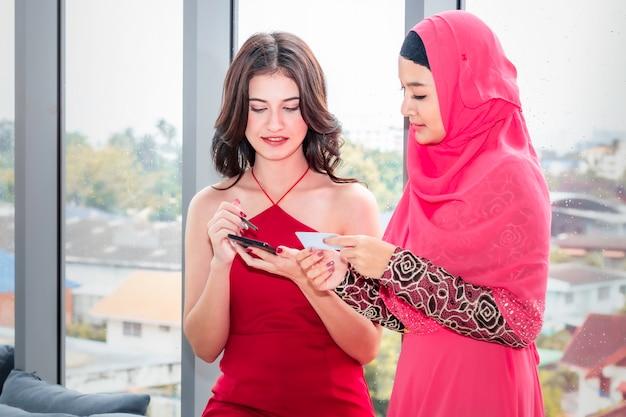 Jeune femme musulmane et amitiés caucasiennes avec téléphone et carte de crédit profitant en shopping Photo Premium