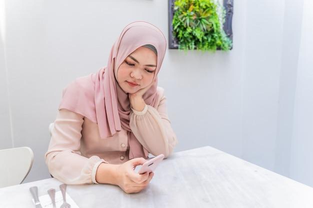 Jeune femme musulmane assise sur une chaise dans la salle blanche à l'aide de téléphone portable en tapant pour un ami. Photo Premium