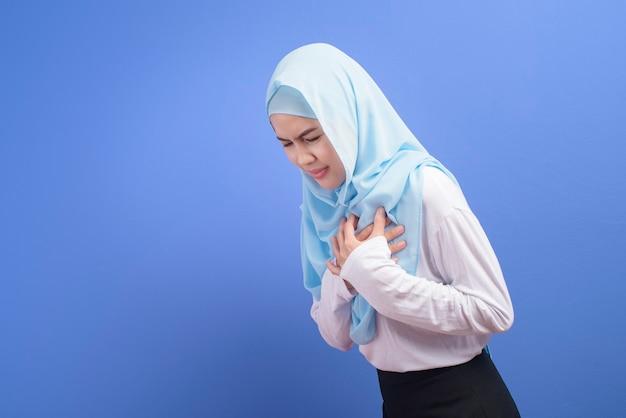 Une Jeune Femme Musulmane Portant Le Hijab Souffrant De Douleurs Thoraciques Sur Le Mur Bleu, Crise Cardiaque Et Concept Médical. Photo Premium