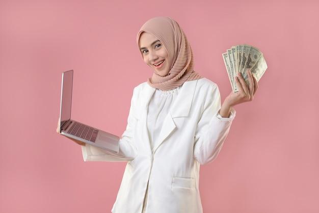 Jeune Femme Musulmane Travaillant En Ligne Sur Un Ordinateur Portable Et Tenant De L'argent Photo Premium
