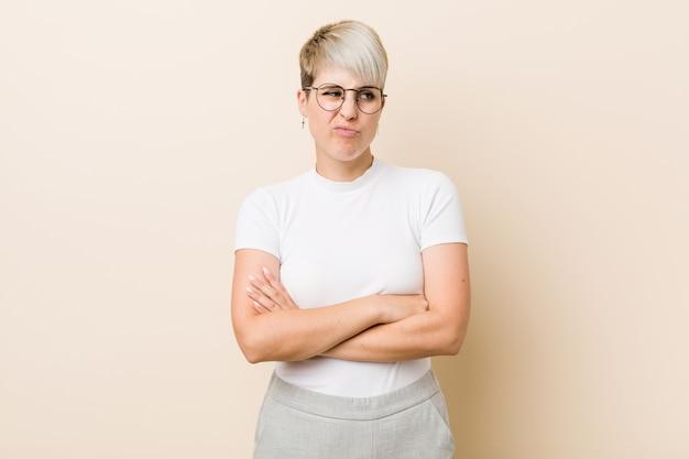 Jeune femme naturelle authentique portant une chemise blanche malheureuse à la recherche à huis clos avec une expression sarcastique. Photo Premium
