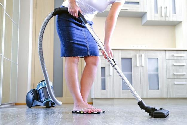 Une jeune femme nettoie l'appartement. dans les mains d'un appareil ménager, aspirateur. Photo Premium