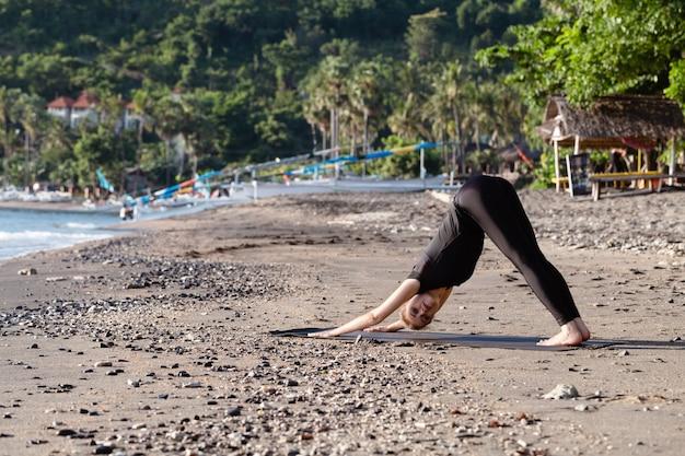Jeune femme en noir faisant du yoga sur la plage de sable asiatique Photo Premium