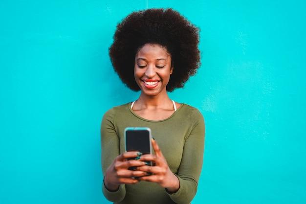 Jeune Femme Noire à L'aide De Téléphone Mobile Intelligent - Fille Africaine En Riant Et Souriant à L'aide De L'application Web Sur Téléphone Portable - Mode De Vie Féminin Et Concept Technologique - Se Concentrer Sur Le Visage Photo Premium