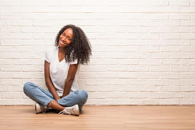 Jeune femme noire assise sur un plancher en bois gai et avec un grand sourire, confiante, amicale et sincère, exprimant la positivité et le succès Photo Premium