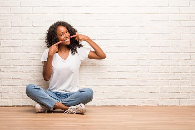 Jeune femme noire assise sur un plancher en bois sourit, pointe la bouche, concept de dents parfaites, dents blanches, a une attitude joyeuse et joviale Photo Premium