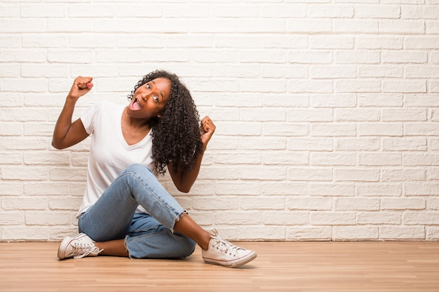 Jeune femme noire assise sur un plancher en bois très heureuse et excitée, levant les bras Photo Premium