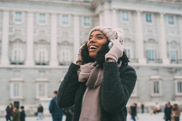 Jeune femme noire, écouter de la musique et danser sur le téléphone portable près du palais royal en hiver Photo Premium