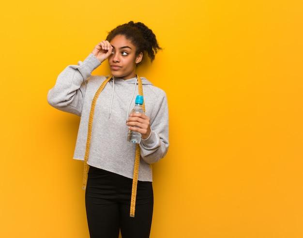 Jeune Femme Noire Fitness Faisant Le Geste D'une Lorgnette. Détenant Une Bouteille D'eau. Photo Premium