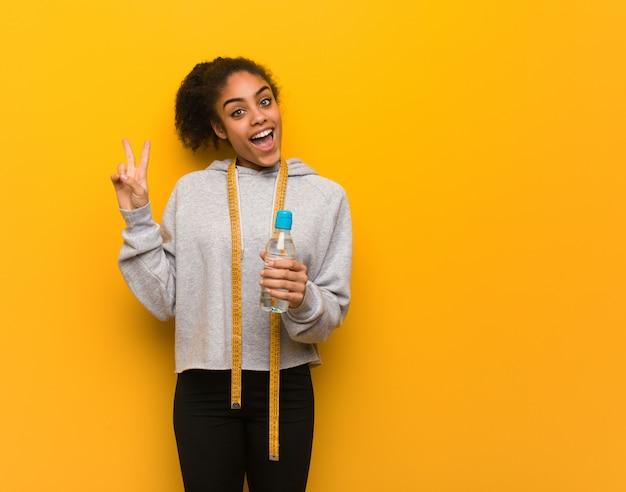 Jeune Femme Noire Fitness Faisant Un Geste De Victoire. Tenant Une Bouteille D'eau. Photo Premium