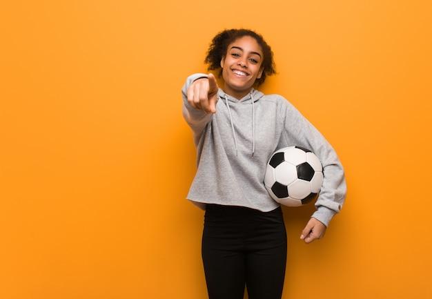 Jeune femme noire fitness joyeuse et souriante. tenir un ballon de foot. Photo Premium