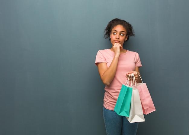 Jeune Femme Noire Pensant à Une Idée. Elle Tient Des Sacs à Provisions. Photo Premium