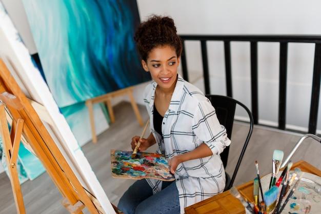 Une Jeune Femme Noire Pensive Artiste En Studio Tenant Un Pinceau. étudiante Inspirée Assise Sur Ses œuvres. Photo gratuit