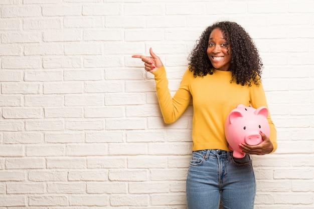 Jeune femme noire pointant sur le côté, souriant, présentant quelque chose Photo Premium