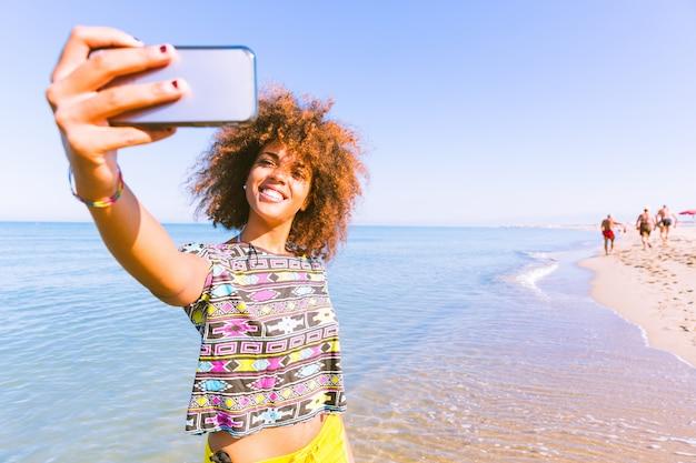 Jeune femme noire prenant un selfie à la plage Photo Premium