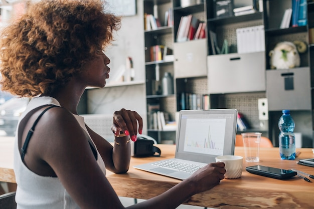 Jeune femme noire à la recherche d'un ordinateur portable et assise dans un bureau de coworking moderne Photo Premium