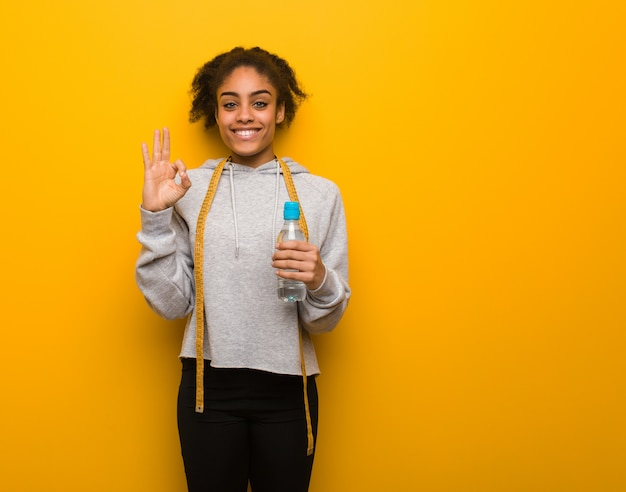 Jeune Femme Noire De Remise En Forme Gaie Et Confiante, Faisant Le Geste Correct. Tenant Une Bouteille D'eau. Photo Premium