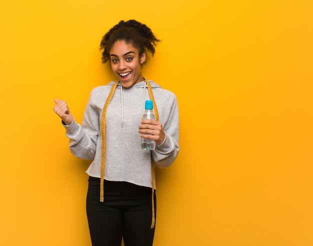 Jeune Femme Noire De Remise En Forme En Souriant Et En Pointant Vers Le Côté. Tenir Une Bouteille D'eau. Photo Premium