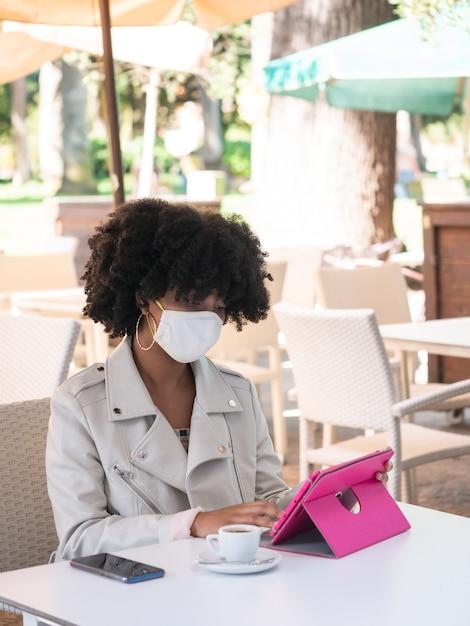 Jeune Femme Noire S'assit Sur Un Café Tout En Travaillant Avec Une Tablette Rose Photo Premium