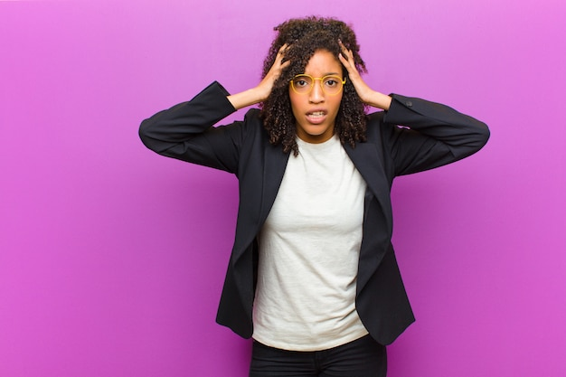 Jeune femme noire se sentant horrifiée et choquée, levant les mains pour se diriger et paniquant face à une erreur Photo Premium