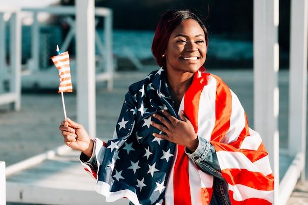 Jeune femme noire souriante avec des drapeaux des états-unis Photo gratuit