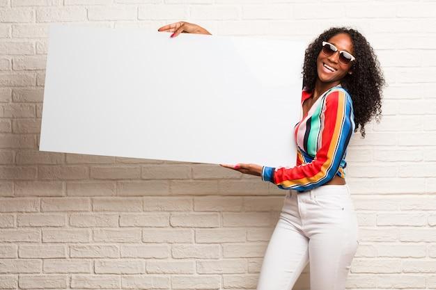 Jeune femme noire tenant quelque chose avec les mains, montrant un produit souriant et gai, offrant un objet imaginaire Photo Premium