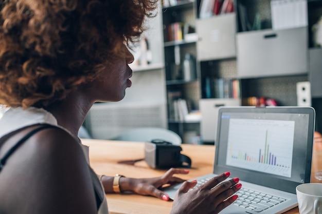 Jeune femme noire travaillant avec un ordinateur portable dans un bureau moderne et la planification d'un projet Photo Premium
