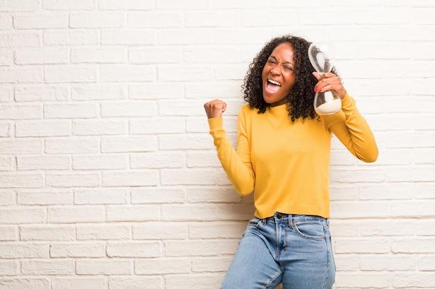 Jeune femme noire très heureuse et excitée, levant les bras, célébrant une victoire ou un succès, remportant le tirage au sort Photo Premium