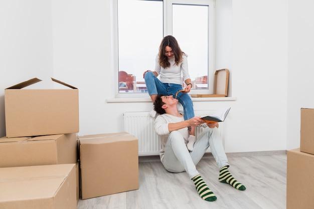 Jeune femme nourrit une tranche de pizza à son petit ami dans leur nouvelle maison Photo gratuit