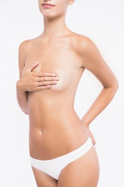 Jeune femme nue avec la main sur la poitrine Photo gratuit