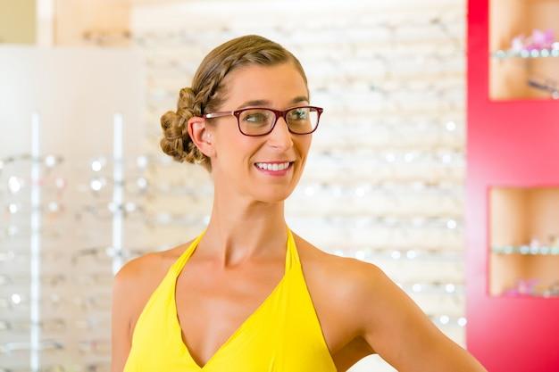 Jeune femme à l'opticien avec des lunettes Photo Premium