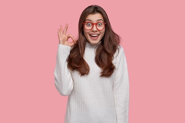 Une Jeune Femme Optimiste Aux Cheveux Noirs Montre Zéro Signe Ou Un Geste Correct, Sourit Largement, Porte Un Pull Blanc, Approuve Tout Ce Qui Est Bon Photo gratuit