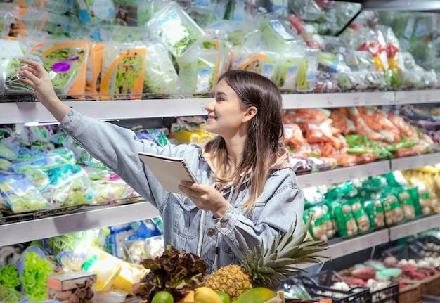Une Jeune Femme Avec Un Ordinateur Portable Achète Des Produits D'épicerie Au Supermarché Photo gratuit