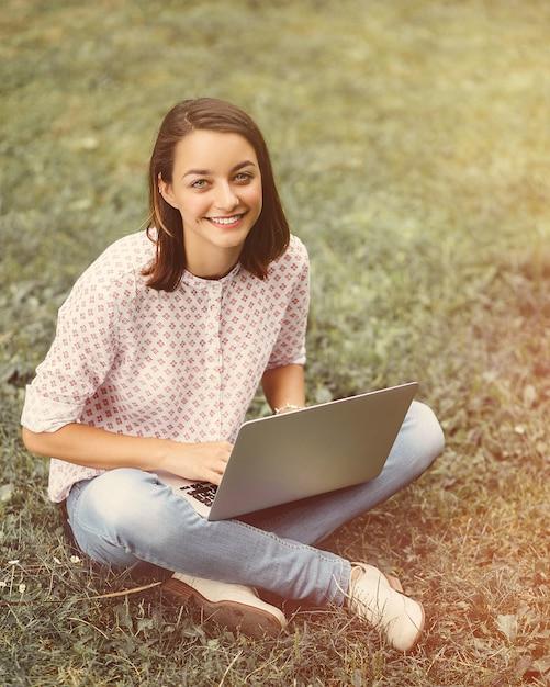 Jeune femme avec un ordinateur portable assis sur l'herbe verte Photo gratuit