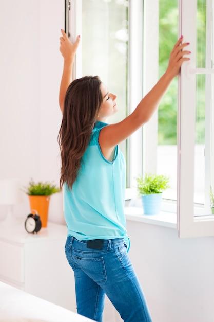 Jeune Femme Ouvrant La Fenêtre Dans Le Salon Photo gratuit