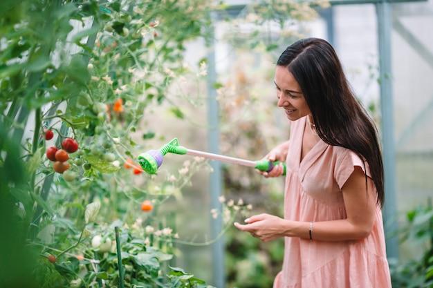 Jeune femme avec panier de verdure et de légumes en serre. temps de récolte Photo Premium