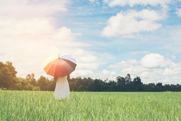 Jeune Femme Avec Un Parapluie Dans La Prairie Photo gratuit