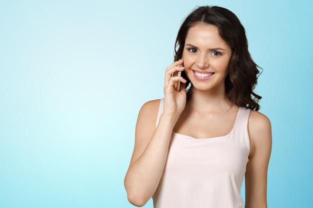 Jeune femme parlant au téléphone mobile Photo Premium