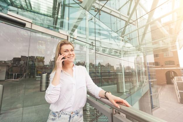 Jeune femme parle au téléphone portable avec un vitrage Photo Premium