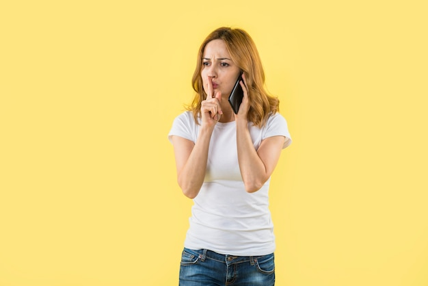 Jeune femme, parler, sur, téléphone portable, faire, geste silence, sur, fond jaune Photo gratuit