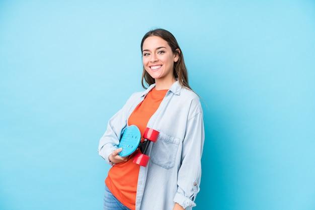 Jeune Femme De Patineur Caucasien Isolé Sur Fond Bleu Photo Premium