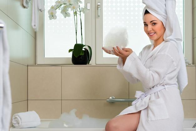 Jeune femme en peignoir dans la salle de bain de l'hôtel Photo Premium
