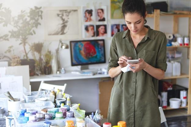Jeune Femme Peintre Attrayante Portant Chemise Décontractée, Debout Dans Son Atelier, Regardant Attentivement Dans Son Smartphone Photo gratuit